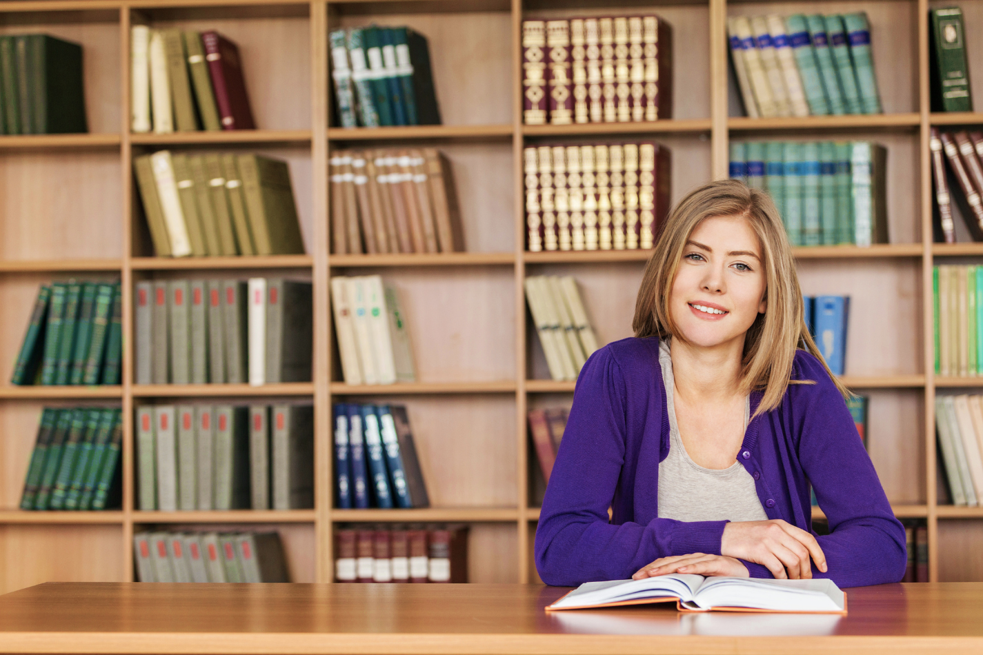 image of a woman smiling at the camera with book if front of her and with a library background