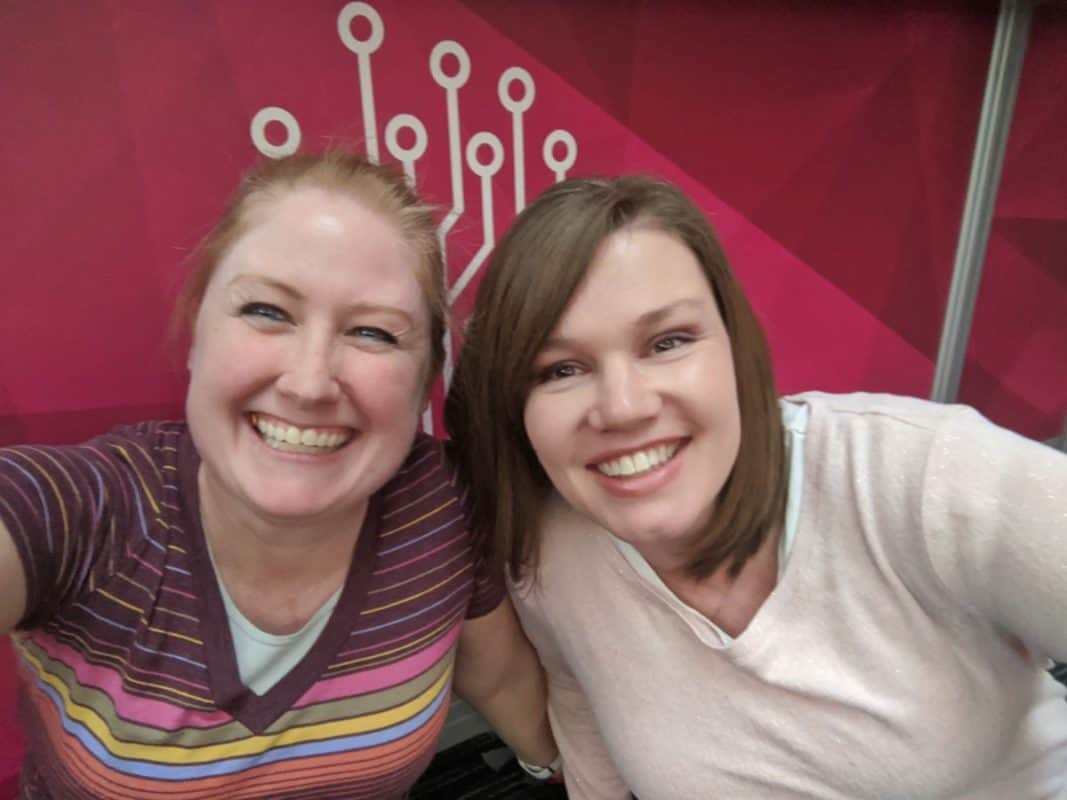 Kimberly and Breanne in front of a pink Roots Tech banner at the 2020 convention in Salt Lake City
